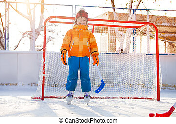 Little boy play hockey standing in gates