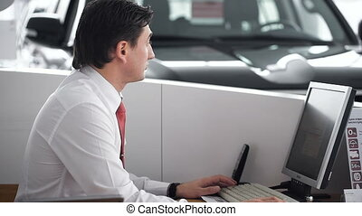 Manager using phone. Car showroom. The manager calls the...