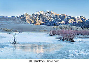 Sand dunes, mountains and creek - Sunrise over frozen Medano...