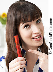 Young Woman Putting On Mascara At Home
