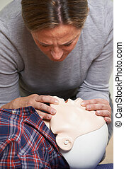 Woman In First Aid Class Performing Mouth To Mouth...