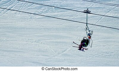 Skiers Passing On Chairlift - Ski-lift takes skiers up...