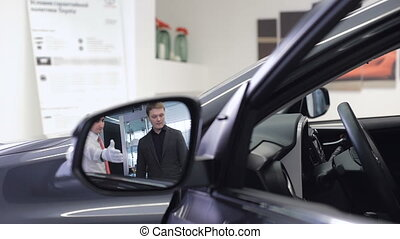 Image of car dealer with client preparing to test drive....