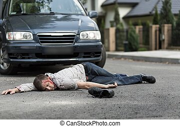 Victim of car accident - Pedestrian hit by a car lying on...
