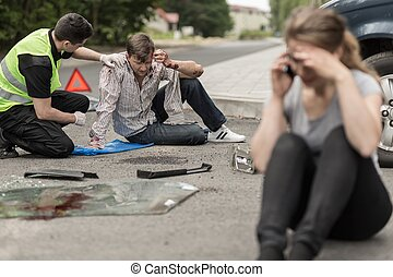 Victims of car accident - People sitting on the road after...