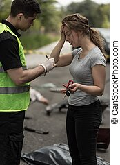 Policeman taking statement - Woman which caused accident is...