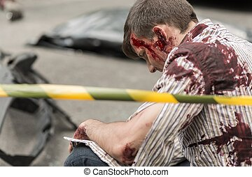 Injured man bleeding - Man is sitting on the road and...