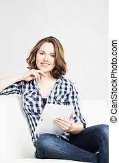 Attractive and young woman with a tablet computer at home.