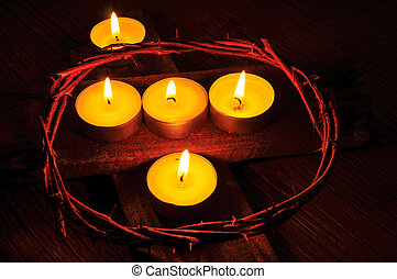a crown of thorns and some lit candles on a wooden cross