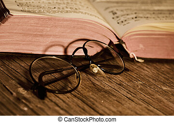 old eyeglasses and books, filtered - closeup of a pair of...