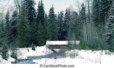 Covered Bridge Over River In Winter - River through snowy...