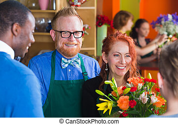 Happy owner of flower shop with staff and customer