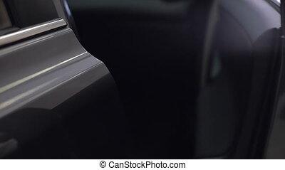Man in white gloves close a car door