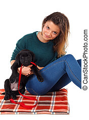 Cute labrador puppy - Woman playing with her black labrador...