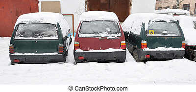 old cars covered with snow - Several old cars standing in...