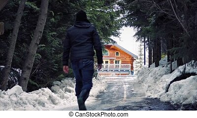 Man Walks Up To House In Snowy Fore - Man walks up the drive...