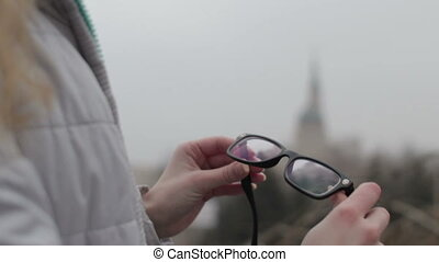 Girl cleaning glasses lens at the park in the city - Blonde...