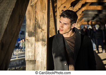 Young man standing on wooden footbridge in Switzerland while...
