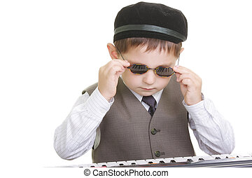 Cute kid adjusting spectacles at piano keyboard against...