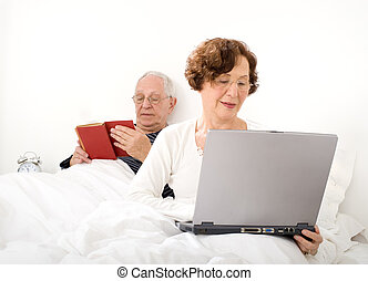 senior couple in bed with laptop and book