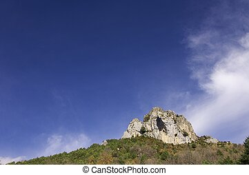 Crag - rocky crag in a forest and blue sky with white clouds...
