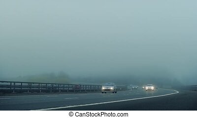 Cars Pass On Highway In The Mist - Cars pass by on road in...