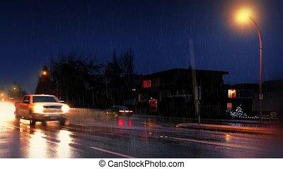 Cars Passing Houses On Rainy Night - Many cars pass on main...