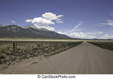 Road to the Mountains - An dirt road traveling toward a...