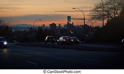 Cars Passing On City Road At Dusk - Vehicles driving past...