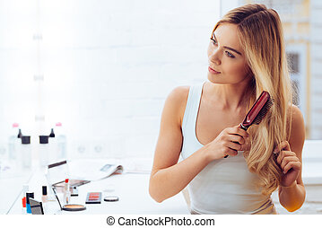 Getting rid of tangles. Beautiful young woman looking at her...