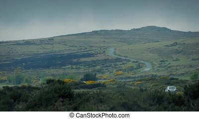 Cars Passing On Road On Moorland - Two cars drive past each...