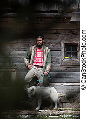 hipster with dog in front of wooden house - handsome young...