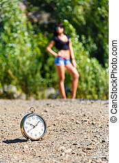 clock on the stone road and blurred girl at sunny day its...