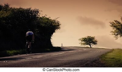 Cyclist Rides Up Hill At Sunset - Man cycles on road in the...