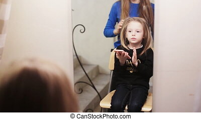 hairdresser combing her hair of cute little girl