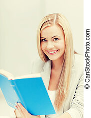 young woman reading book - picture of smiling young woman...