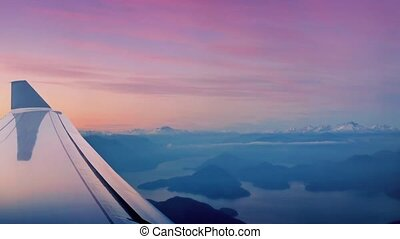 Flying Over Mountains And Lakes - View of plane wing flying...