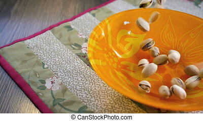 Pistachio nuts falling into bowl