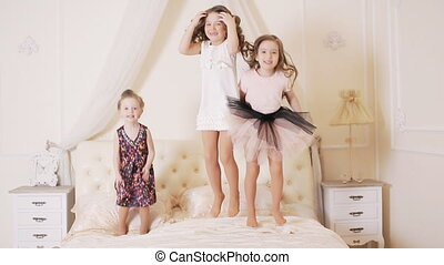 little girls jumping on the bed