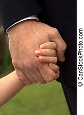 Father and Son Holding Hands - A son tightly holds his...