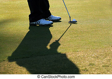 Golfer Lines Up His Putt - A golfer is about to putt the...