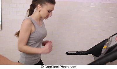 Girl runs on a treadmill in a gym