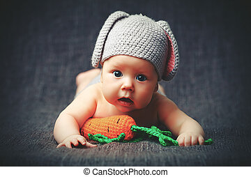 happy baby child in costume a rabbit bunny with carrot on a...