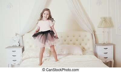 cute girl jumping on the bed - little kid jumping and...