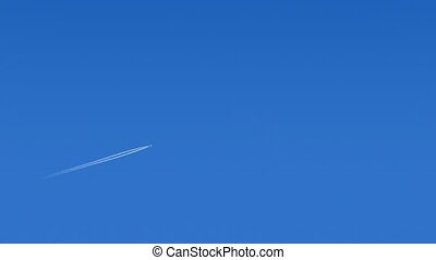 Plane Flies Across Blue Sky - 747 High above flies over on...