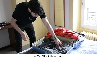 Young man trying to close his suitcase - Close-up of...