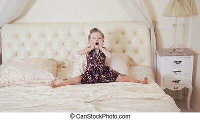 happy girl act the ape on the bed - cute girl jumping on the...