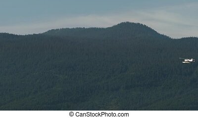 Seaplane Flies Past Mountain Forest - Wide shot of seaplane...