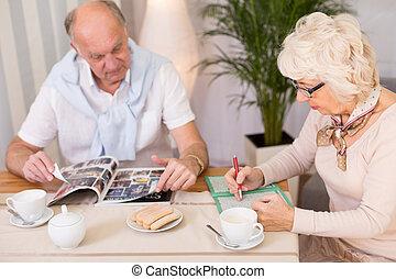 Brain training for seniors - Senior woman doing crosswords...
