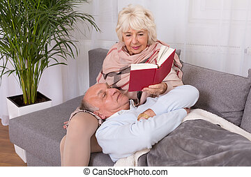 I feel so good with you. - Senior woman reading book to her...